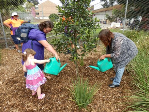 Tom's sister Kim on the right &  her niece & grandniece on the left watering the tree for the first time.  Marrickville Council even brought watering cans for the family to water the tree.