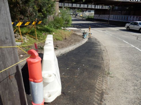 The bitumen area is where the swale & planted area around the swale used to be.  Cyclists will soon have a dual cycleway here that goes onto the footpath under the bridge.
