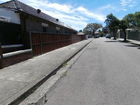A street in Marrickville.  No overhead powerlines and footpaths of equal size on both sides of the road.