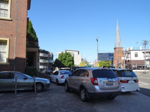 Unofficial car park.  I counted 13 cars, & there were more parked on the footpath beside the building on Petersham Road.