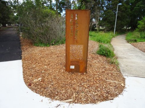Sign for Cooks River Valley Garden.  To the left you can see new bitumen has been laid alongside the Fig trees from the car park