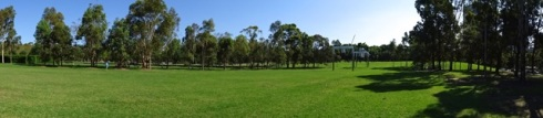 A grassed area with the hedged garden, rows of trees and waterplay in the distance.
