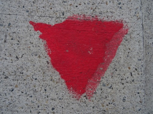 Red triangle painted on the footpath of those who opt in to Marrickville Council's No Spray Register.