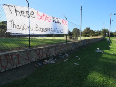 Sign hung up in Ewen Park with plastic bottles from the Cooks River underneath.