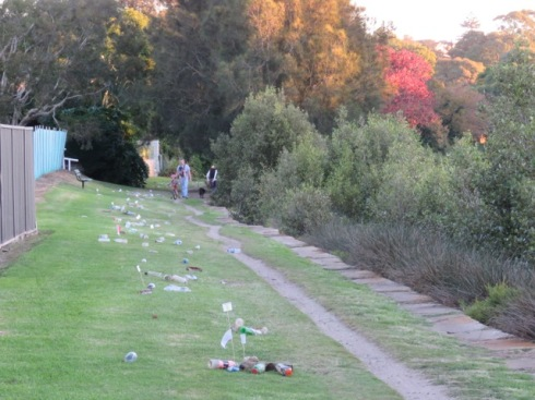 "Plastic bottles retrieved from the Cooks River today strewn along the path on the Lang Road side of the river.  Small signs say, ""I 'm worth 10c."""