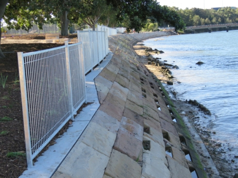 New fencing, new sloped sandstone riverbank wall and slots for plants.